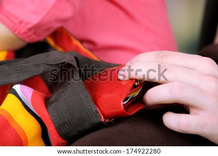 Pickpocket are stealing wallet from bag, close up - stock photo