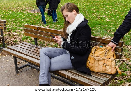 Pickpocket stealing handbag while woman using mobile phone on bench in park - stock photo