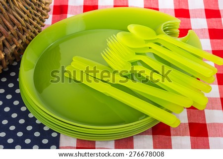 Picnic basket and plastic dishes on red, white and blue tablecloth indicative of the American Flag.  Traditional July 4th picnic scene. - stock photo