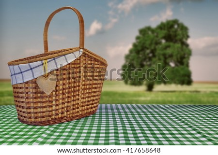 Picnic Basket Closeup On The Green Checkered Tablecloth And Summer Toned Landscape With Alone Tree In The Field In The Background