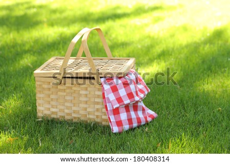 Picnic basket in grass - stock photo