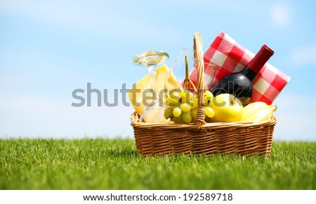 Picnic basket on green field - stock photo