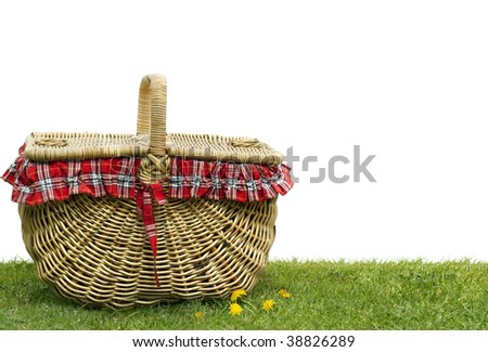 Picnic basket on green grass, over white background.  Lots of copy space. - stock photo