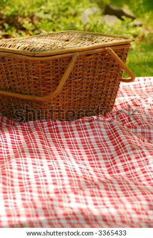 picnic basket on red & white tablecloth - stock photo
