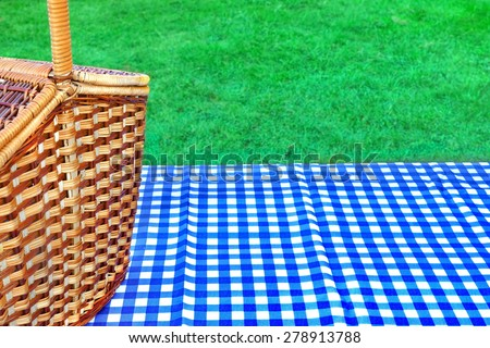 Picnic Basket On The Table With Blue White Checkered Tablecloth. Summer Lawn In The Background - stock photo