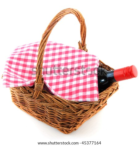 picnic basket with a bottle of wine and checkered cloth - stock photo