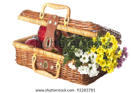 Picnic basket with apples and flowers - stock photo