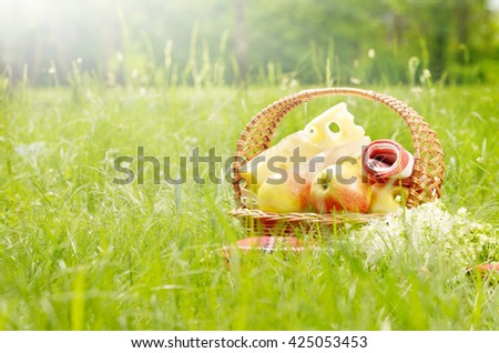Picnic basket with apples bananas and cheese on green grass