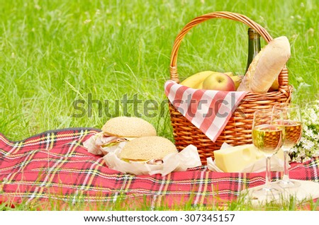 Picnic basket with apples bread cheese wine and sandwiches