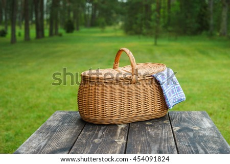 Picnic basket with blue white checkered tablecloth on wooden table. Summertime weekend break concept - stock photo