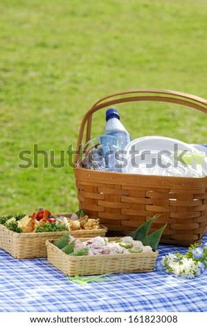 Picnic basket with cutlery and food on blue drop cloth. - stock photo