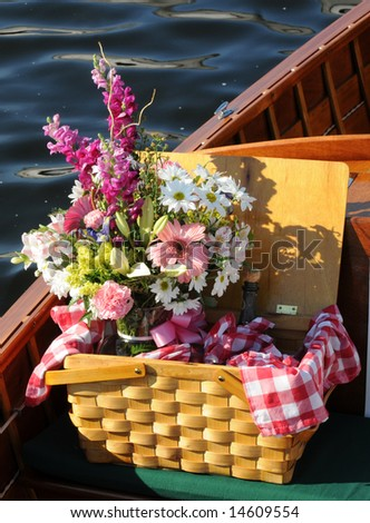 Picnic basket with flowers and bottle of wine - stock photo