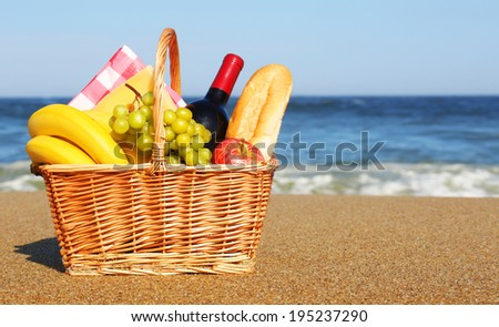 Picnic basket with food on the beach  - stock photo