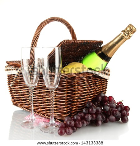 Picnic basket with fruits and bottle of champagne isolated on white - stock photo