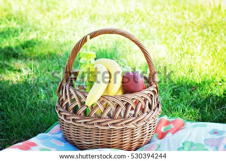 Picnic basket with fruits on lawn