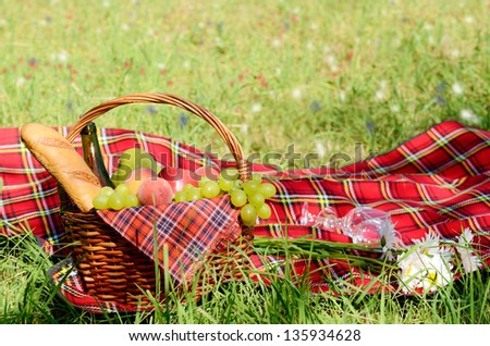 Picnic basket with red napkin fool of fruits, bread and wine
