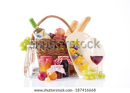 picnic basket with wine, fruits and summer hat isolated on white  - stock photo