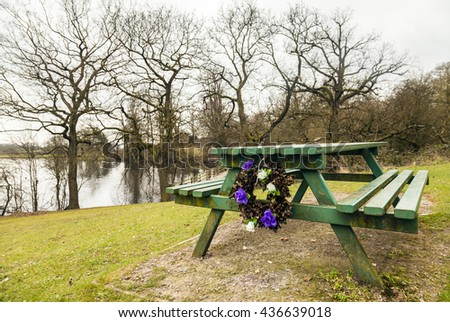 Picnic bench at a local beauty spot with the remains of a memorial floral reef tied to it. - stock photo