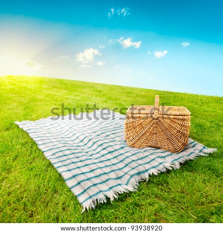 Picnic blanket and basket in a sunlit grassy meadow - stock photo