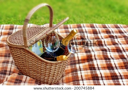 Picnic blanket and basket in the grass. Champagne  wine and glasses in the basket. - stock photo