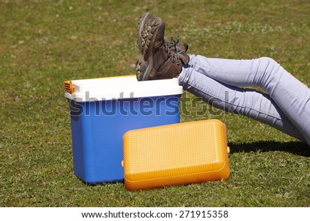 Picnic cooler in the grass and trekking boots in Spain. Horizontal - stock photo