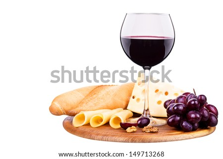 picnic lunch on a wooden board including a wine,bread,cheese and grapes