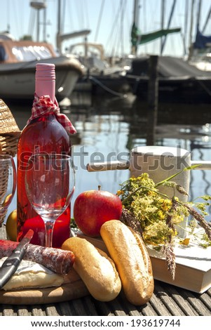 Picnic near the water line with boats on the background - stock photo
