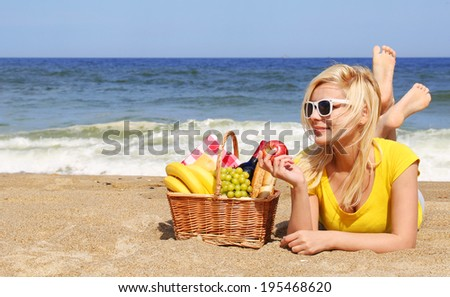 Picnic on the Beach. Blonde Young Woman with Basket of Food on the Shore.  - stock photo