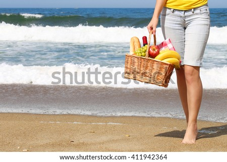 Picnic on the Beach. Female Legs and Basket with Food on on the Shore.