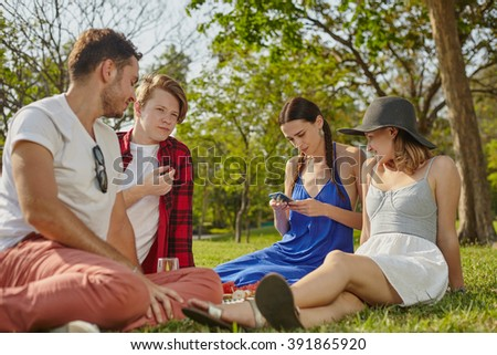 Picnic party friendly young people on the grass in the park in personal interaction - stock photo