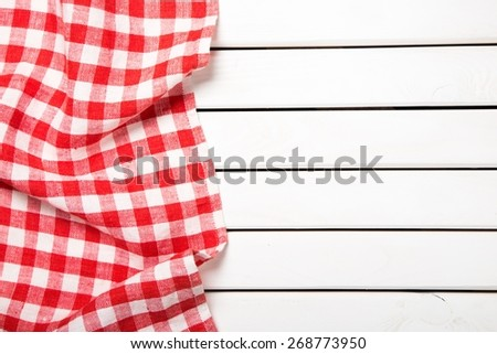 Picnic. Red folded tablecloth over bleached wooden table - stock photo