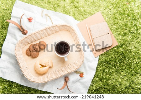 picnic setting on meadow, relaxing on holiday - stock photo