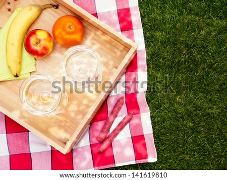Picnic setting with fruit and wine, overhead view - stock photo
