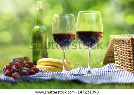 Picnic setting with red wine glasses bottle and picnic hamper basket  - stock photo