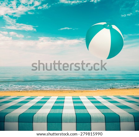Picnic table at the beach with flying beachball - stock photo