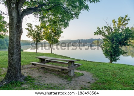 Picnic table by the side of a lake on a summer morning - stock photo