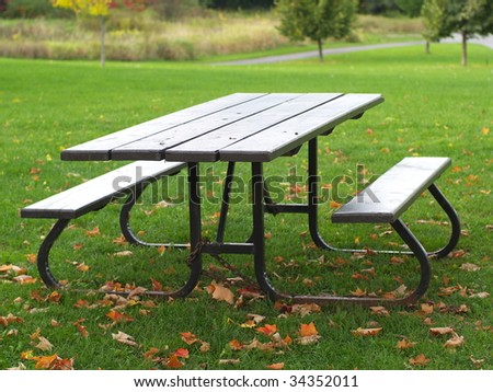 Picnic table in autumn - stock photo