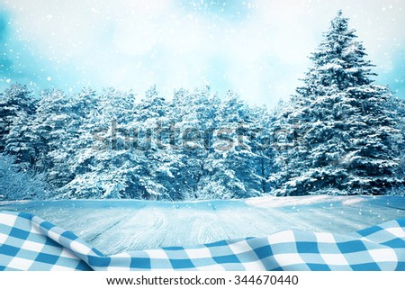 Picnic table in winter forest with blue tablecloth with space for your object - stock photo