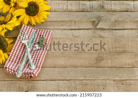 Picnic Table Setting with Pretty Cheerful Sunflowers, Silverware, red  white checked napkin, brown Rustic Wood Board Background, empty room or space for copy, text, your words.  Horizontal