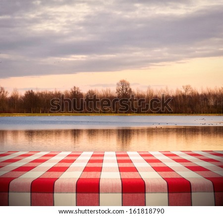 Picnic table template with red checkered tablecloth on sunset lake background - stock photo