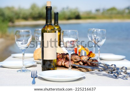 Picnic table with skewers and wine, close-up