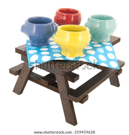 picnic table with soup bowls isolated over white background - stock photo
