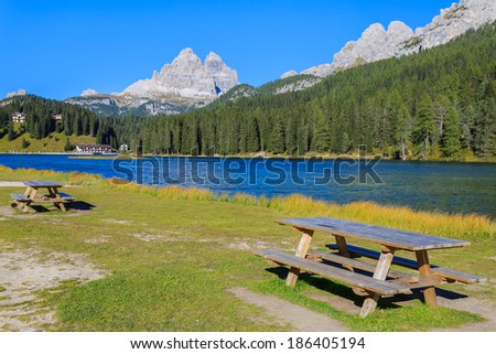 Picnic tables and beautiful alpine lake Misurina in summer time, Dolomites Mountains, Italy - stock photo