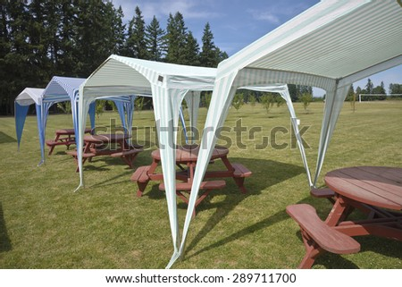 Picnic tables and tent gazebos on an outdoor lawn Canby Oregon. - stock photo