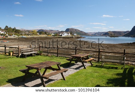 Picnic tables with the village of Plockton and Loch Carron in the background - stock photo