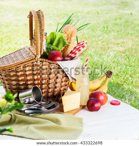 Picnic Wattled Basket Green Grass Setting Food Bread Drink Juice Cheese Pears Banana Summer Time - stock photo