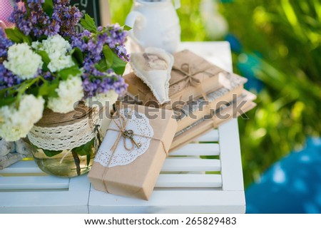 Picnic white table with beautiful bouquet flowersand boxex,books
