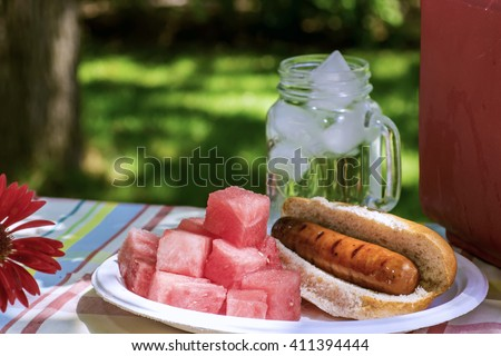 Picnic with Brats, Watermelon, and Ice Water in a Red Cooler in the Shade - stock photo