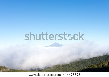 Pico de Teide, the highest mountain in Spain on the Island Tenerife. Huge clouds from trade winds over the national park Garajonay on La Gomera. The clouds comes from the Azores in circa 800m altitude - stock photo