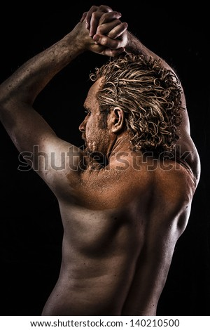 Pictish warrior covered in mud and naked - stock photo